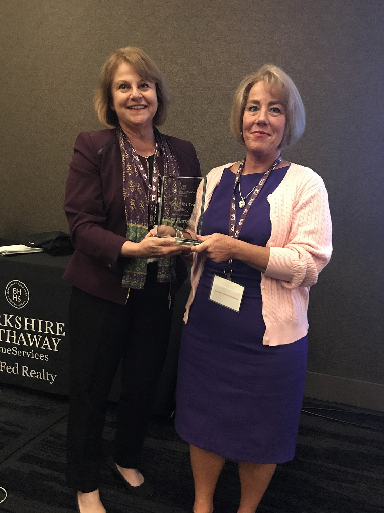 Regional president Terri Bracciale (left) presents the Baltimore metro region ASA of the Year Award to Kelli Hartman (right) of the Ocean City West office.